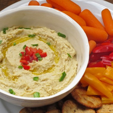 Hummus on game day in a bowl with crackers, carrots and bell pepper strips.