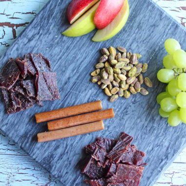 A beef jerky snack board with different types of beef jerky, pistachios, grapes and sliced apples make a fun after school snack. Processed meat or prepared meat can be eaten as part of a healthful diet.