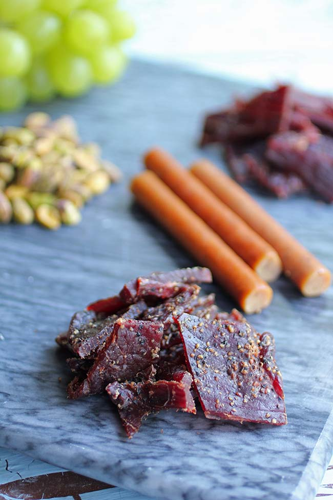 A beef jerky snack board with different types of beef jerky, pistachios, grapes and sliced apples make a fun after school snack. You do have permission to eat processed meat (prepared meat).