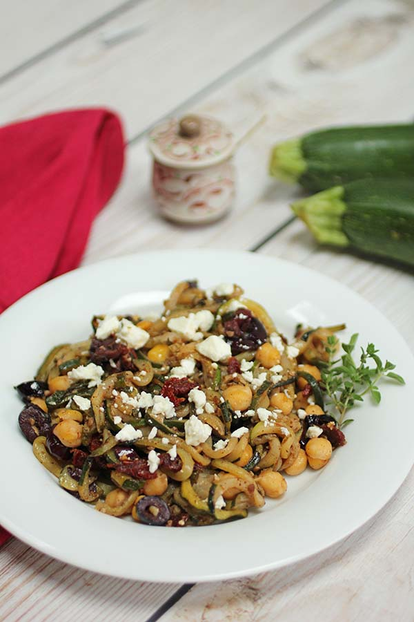 Spiralized zucchini or zoodles are cooked with Middle Eastern spices za'atar and sumac. Kalamata olives, chickpeas, sundried tomatoes and feta cheese add balance to this zucchini side dish.