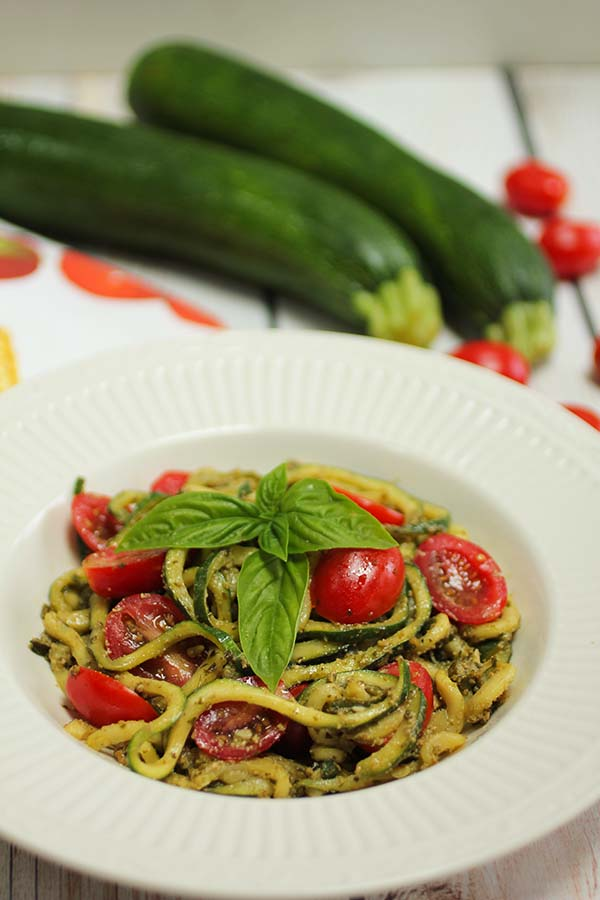 Zucchini noodles or zoodles tossed with pesto sauce and sliced grape tomatoes