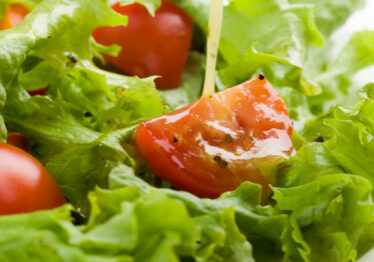 A plate of salad with fresh lettuce and tomato being drizzled with vinaigrette dressing.  Shallow DOF.